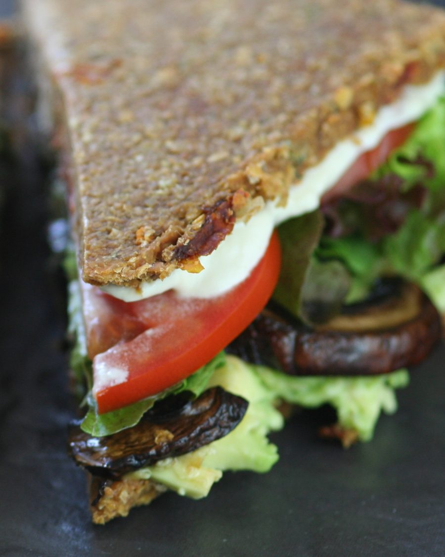 Raw vegan zucchini bread sandwich on a black background