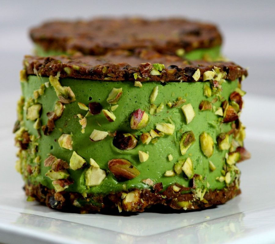 cacao pistachio ice cream sandwich on a white plate