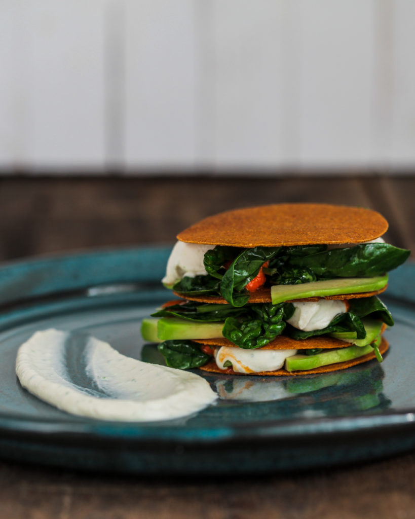 Sour cream avocado napoleon on a blue plate and wooden background