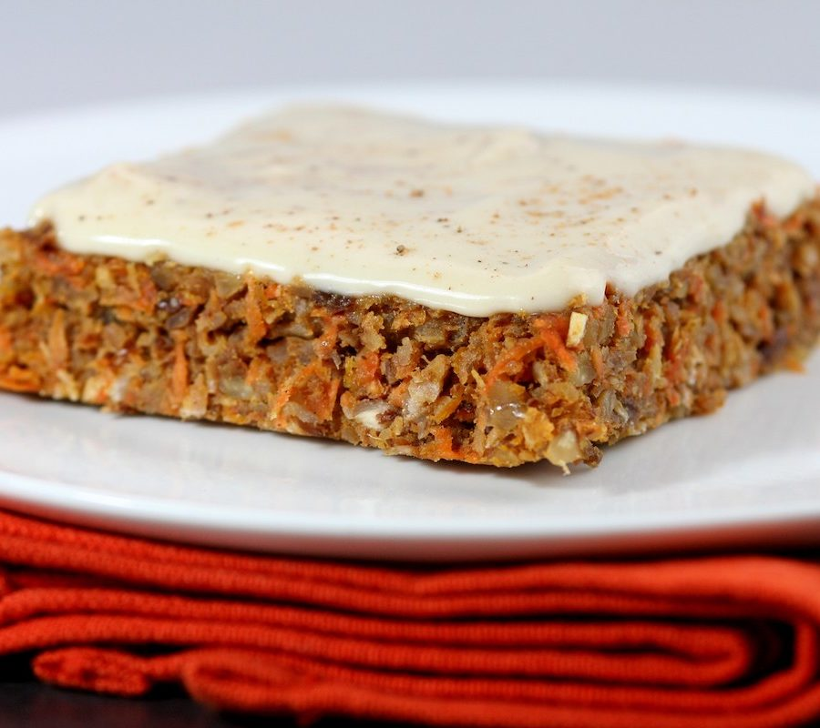 Raw carrot cake on a white plate with an orange napkin