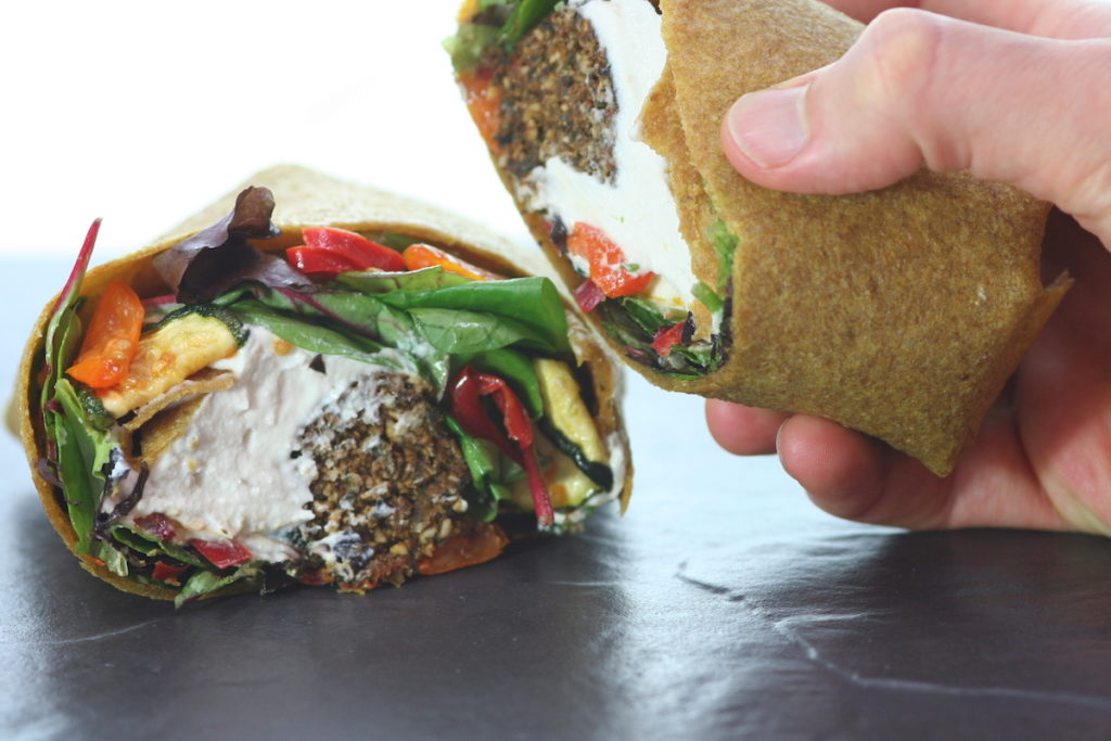 Raw falafel hummus and veg wrap on a black surface