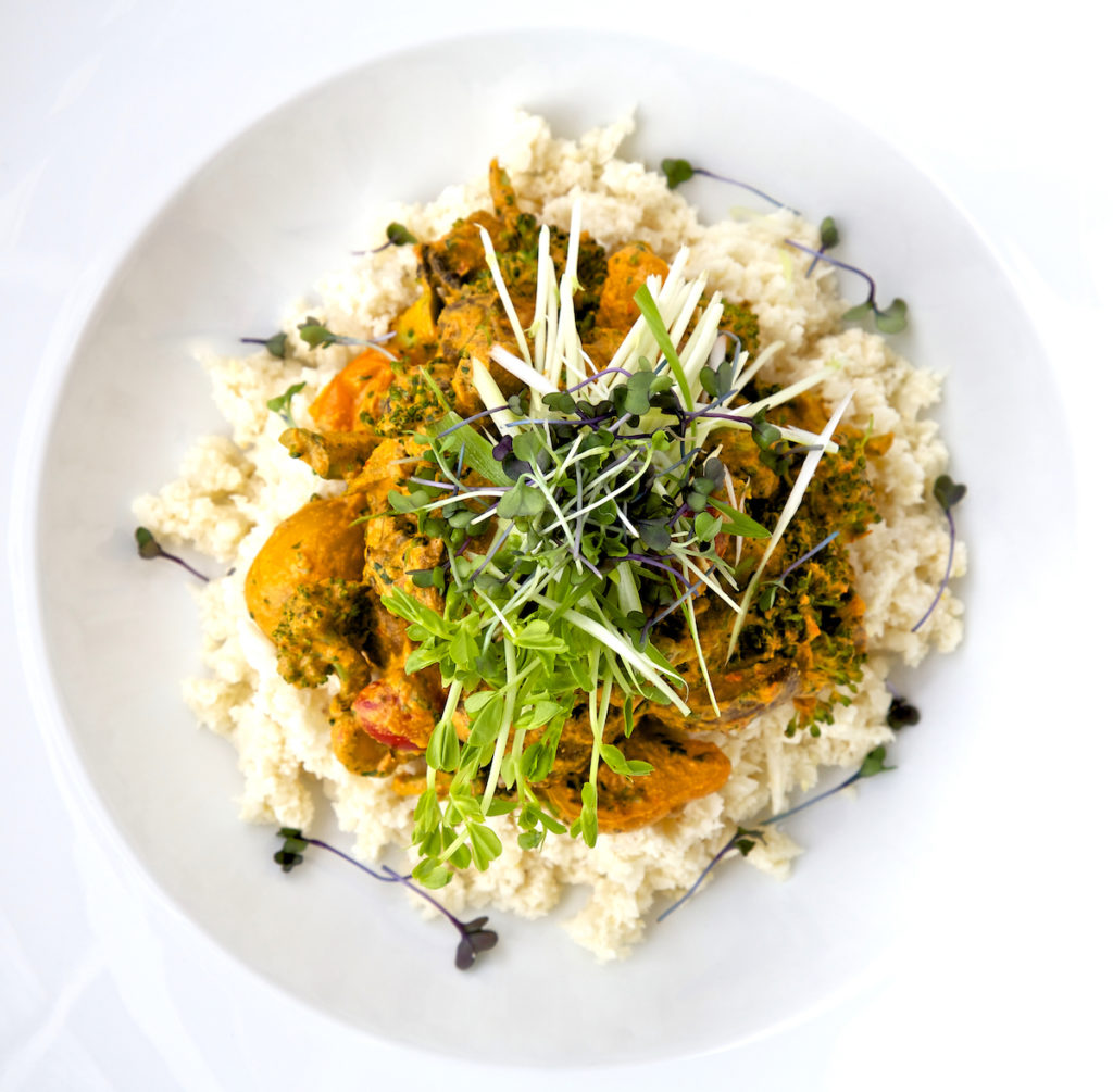 Raw curry overhead shot with microgreens on top, in a white bowl