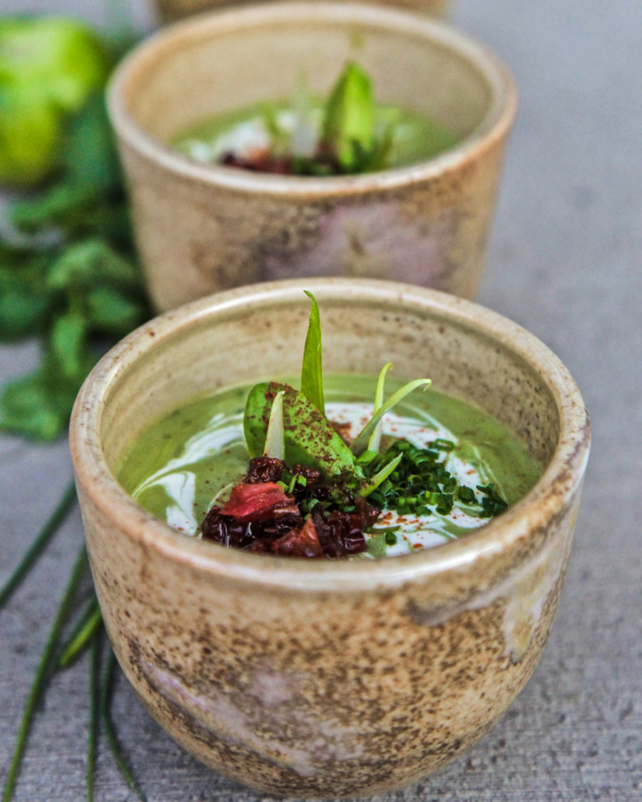 Avocado lime soup in bowls on a concrete surface