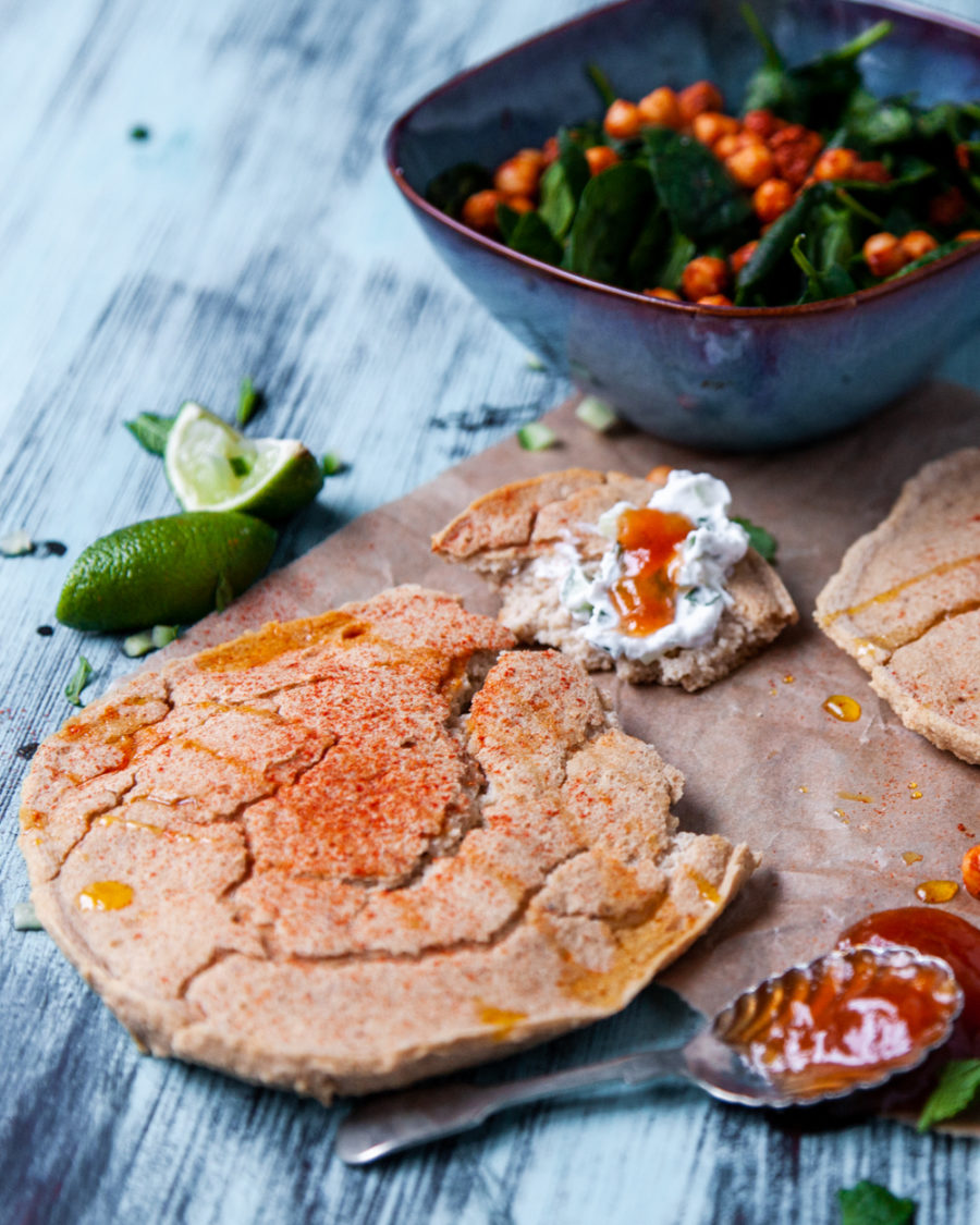 Raw vegan naan bread with coconut yoghurt and chutney on a blue background