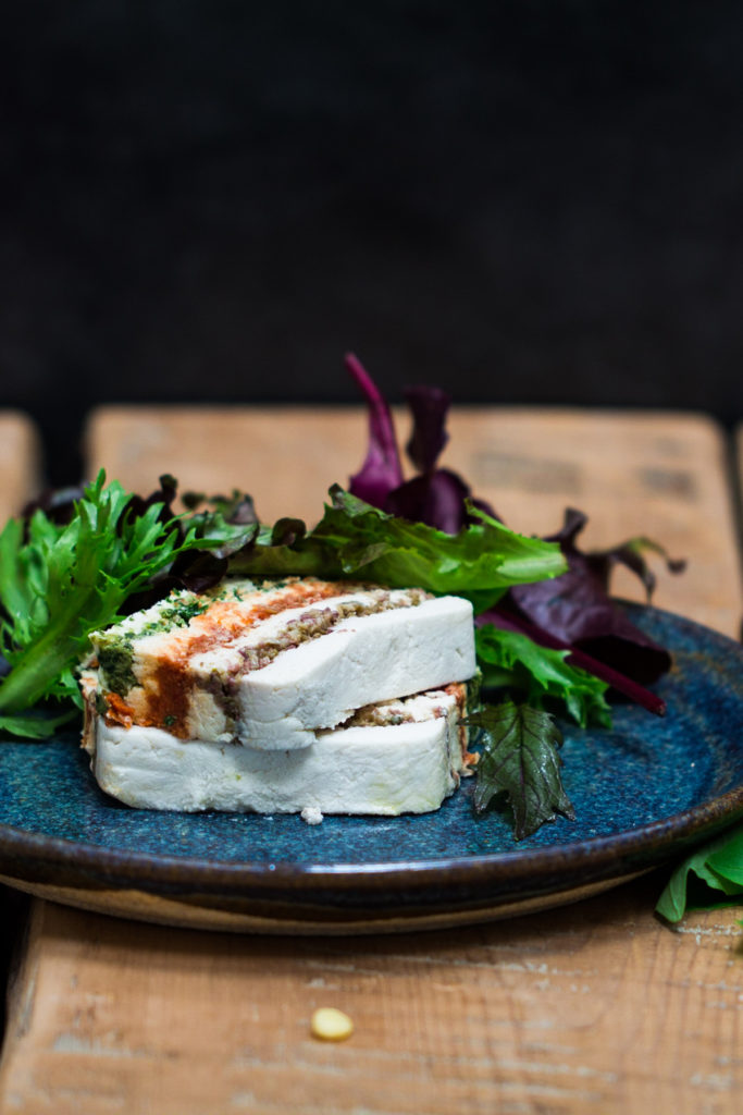 The Almond Cheese Terrine is stacked into two layers with salad greens on the side. The dish is served in a blue plate on a wooden table.