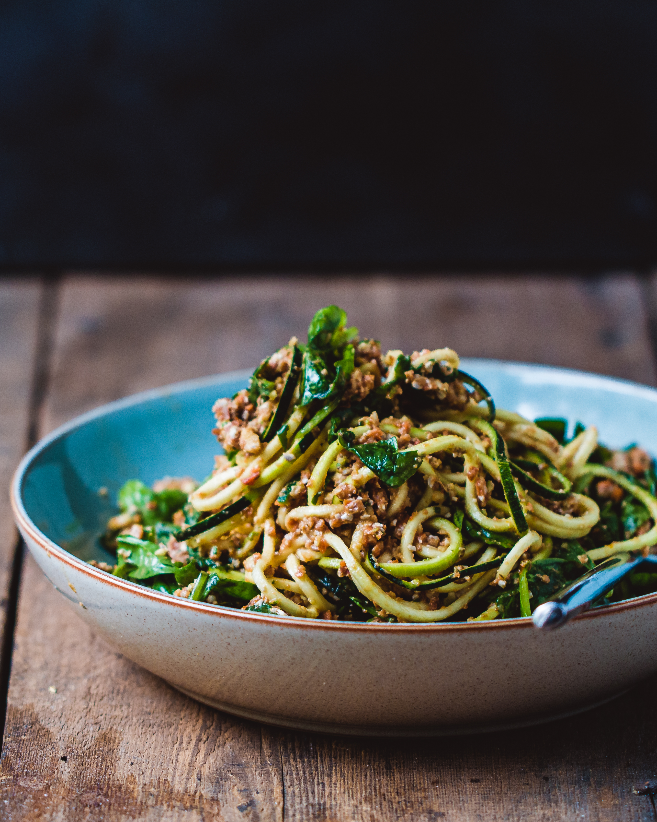 Raw vegan zucchini spaghetti bolognese in a blue and white bowl on a wooden surface