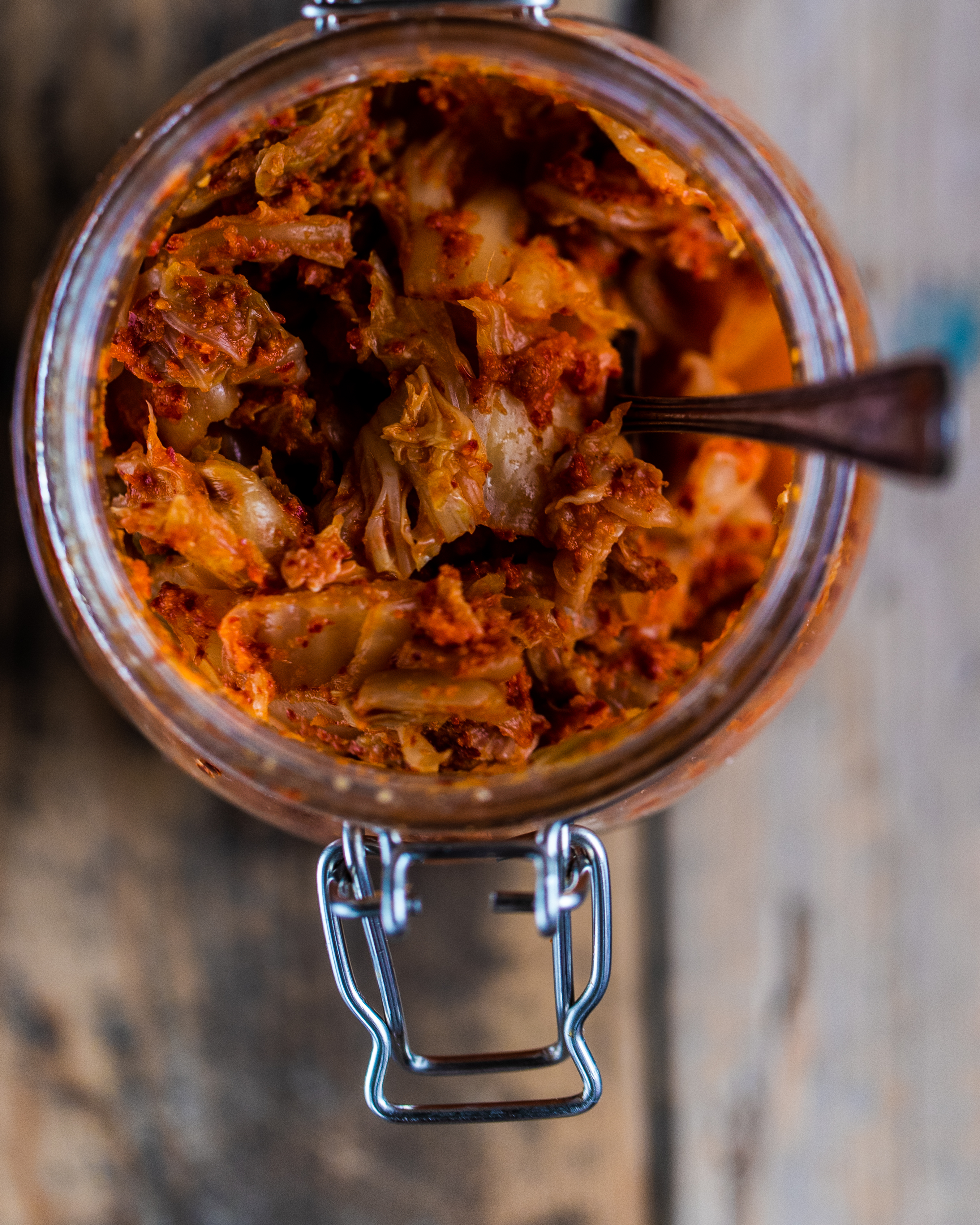 Overhead shot of vegan kimchi in a glass jar on a wooden surface