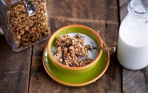 Hemp granola with almond milk in a green bowl on a wooden background