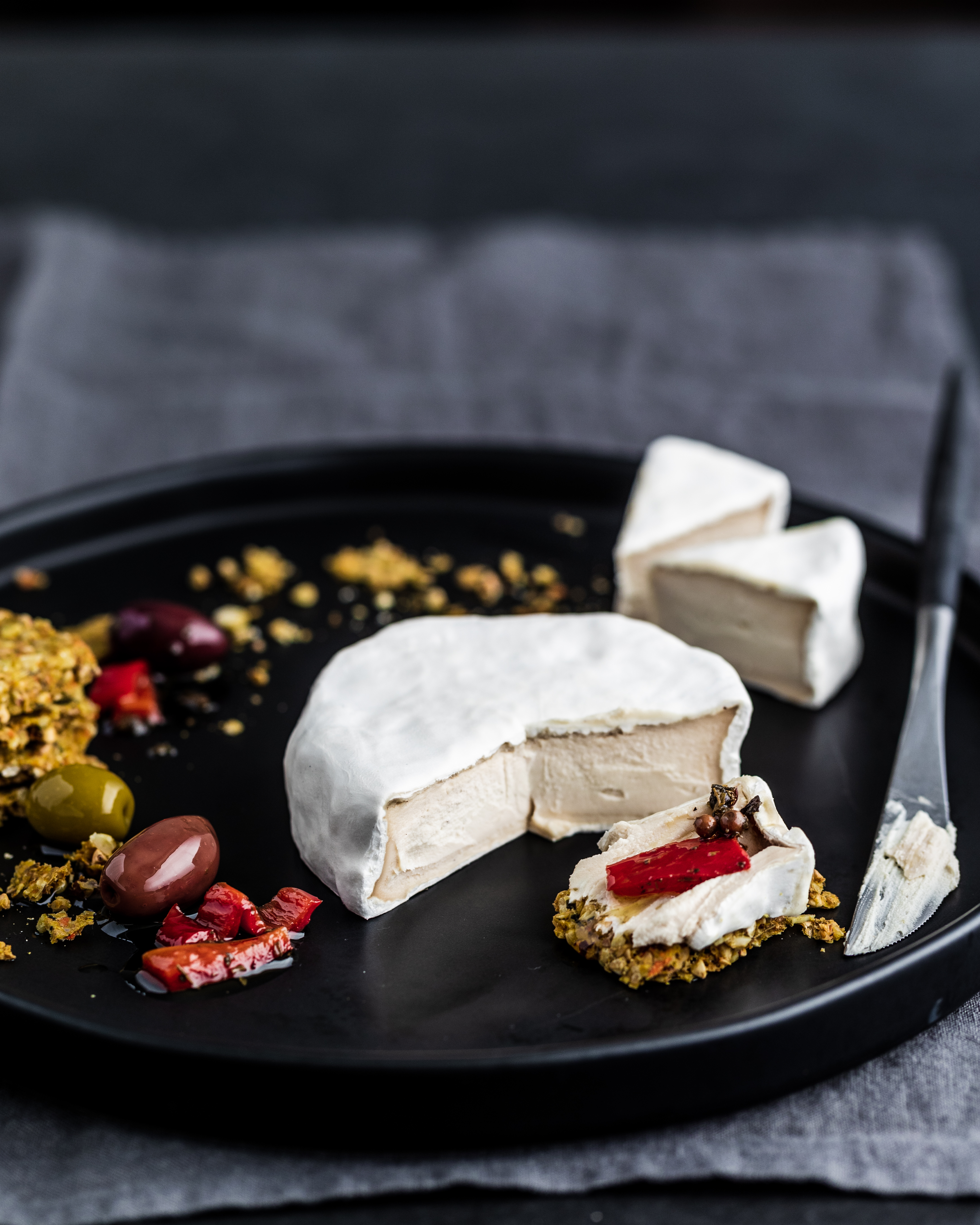 cashew nut camembert cheese on a black plate with crackers, olive and red peppers