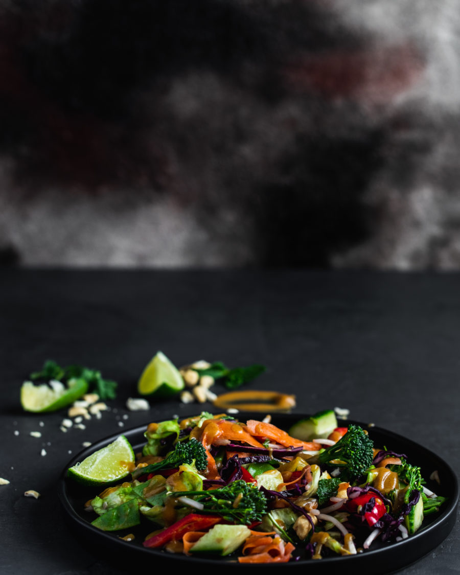 Asian chopped salad on a black plate with lime and chopped nuts