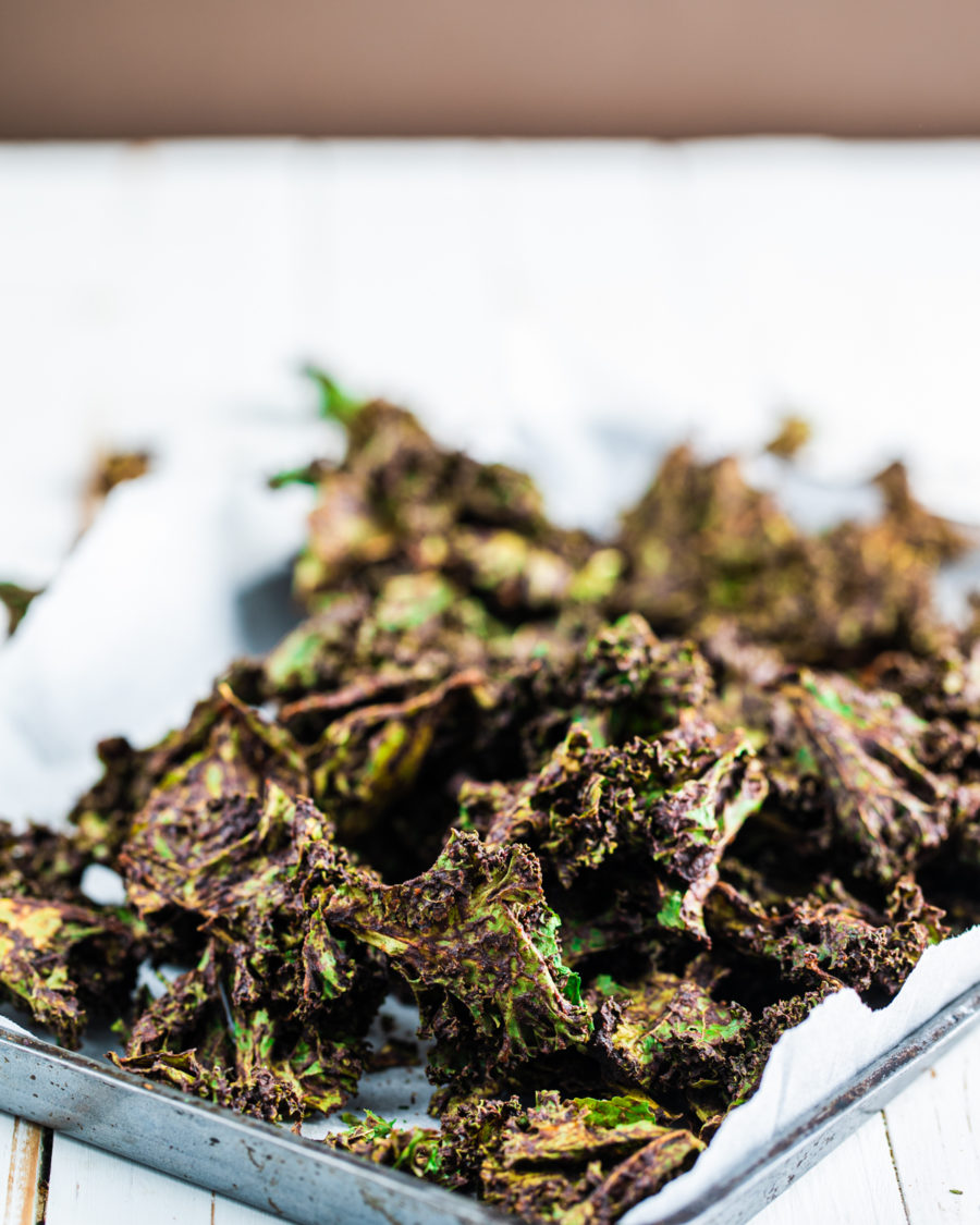 Raw dehydrated kale chips in a baking pan on a white background