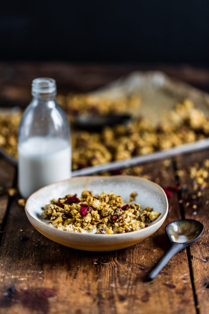 Hemp granola with almond milk in a white bowl on a wooden background