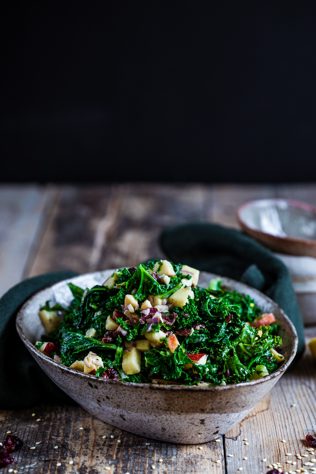 Cranberry & apple kale salad in a bowl on a wooden background.