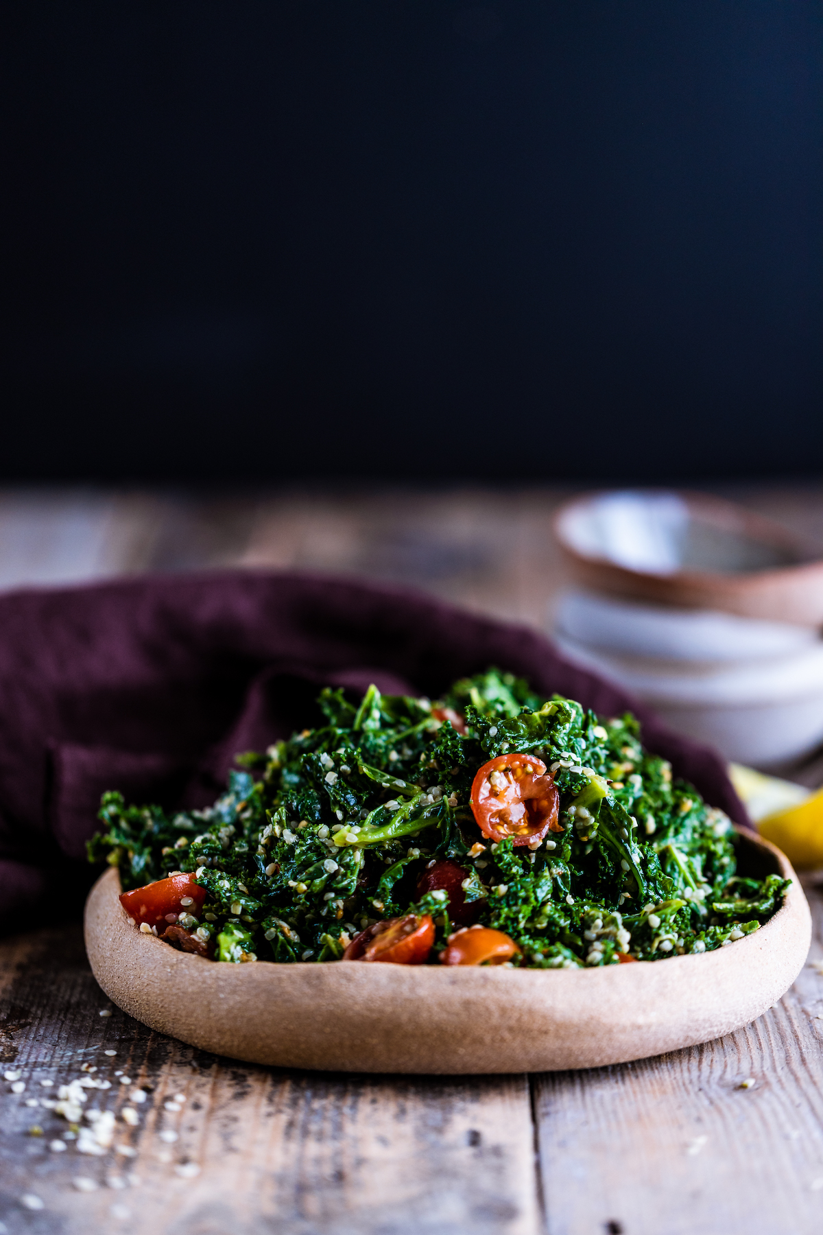 Kale avocado salad in a brown bowl on a wooden surface