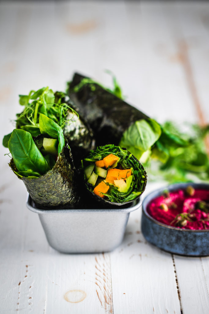 Raw nori wraps with a beet dip in a tray on a white board