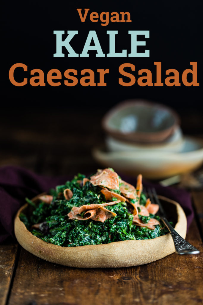 Vegan kale caesar salad in a brown bowl on a wooden background