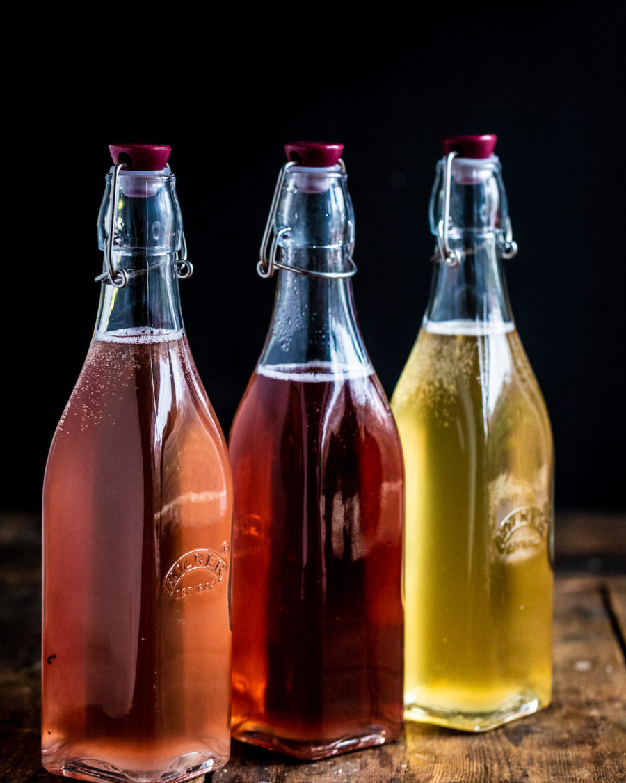 Three different flavours of water kefir in glass bottles