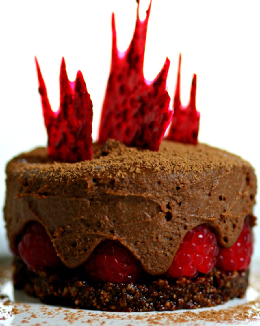 The Chocolate Raspberry Cake with Ginger Chocolate Mousse is dusted with cacao powder on top of a white table
