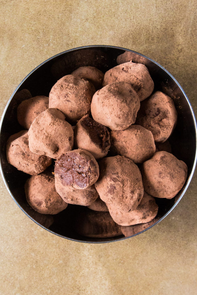 Raw Chocolate balls covered in cacao powder on a silver bowl.