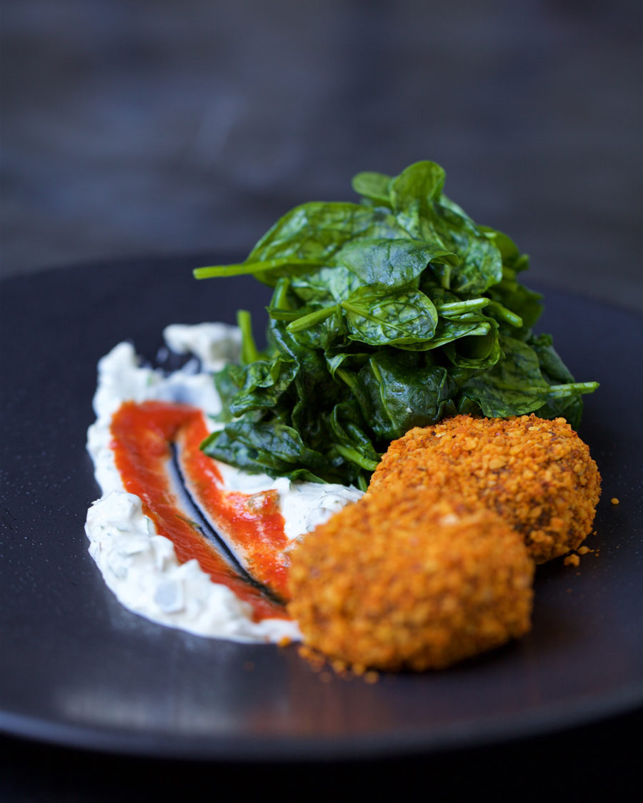 There are two croquettes served in a gray plate with the tartar and sweet chilli spread accross. There is also the wilted spinach on the side of the croquettes.
