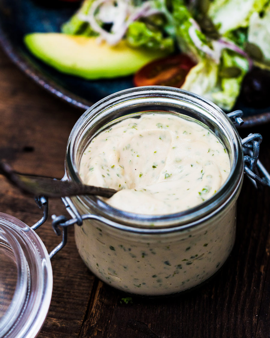 The Caesar dressing is inside a glass fermenting jar on a wooden table.