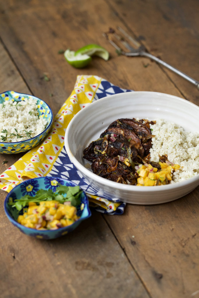 The dish is served on a white bowl on top of a colorful table napkin with some additional mango salsa and cauliflower coconut rice served on the side.