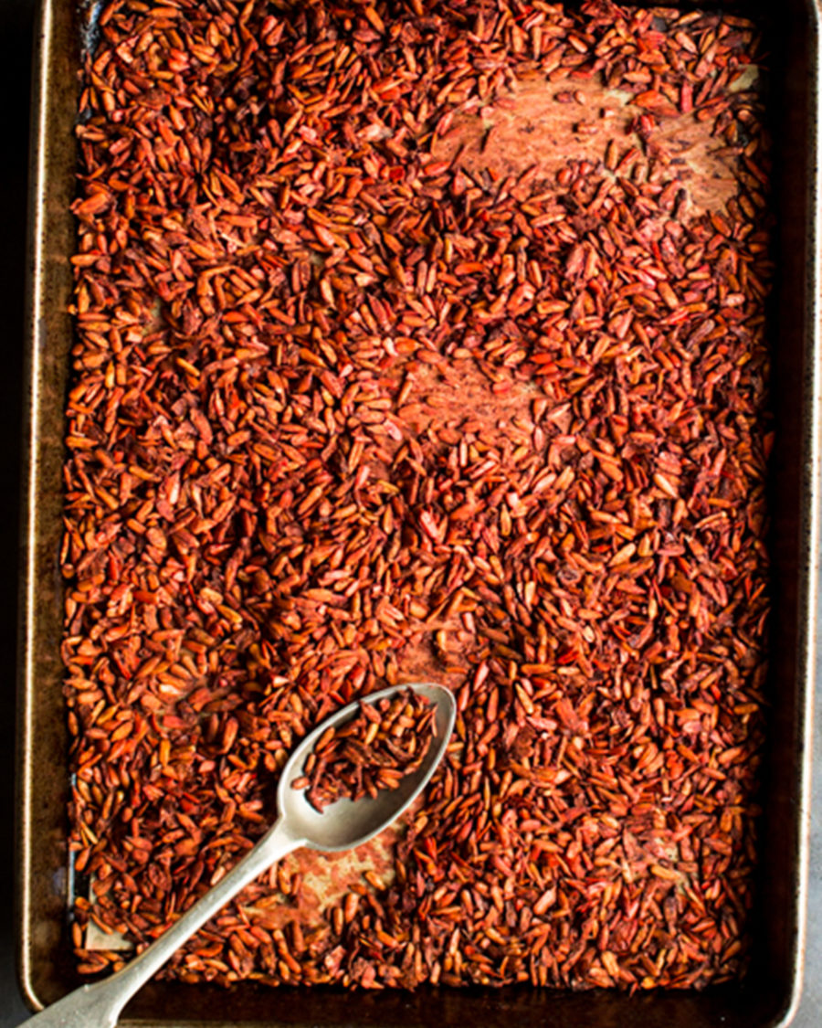 Jerk spiced sunflower seeds on a black baking tray with a silver spoon