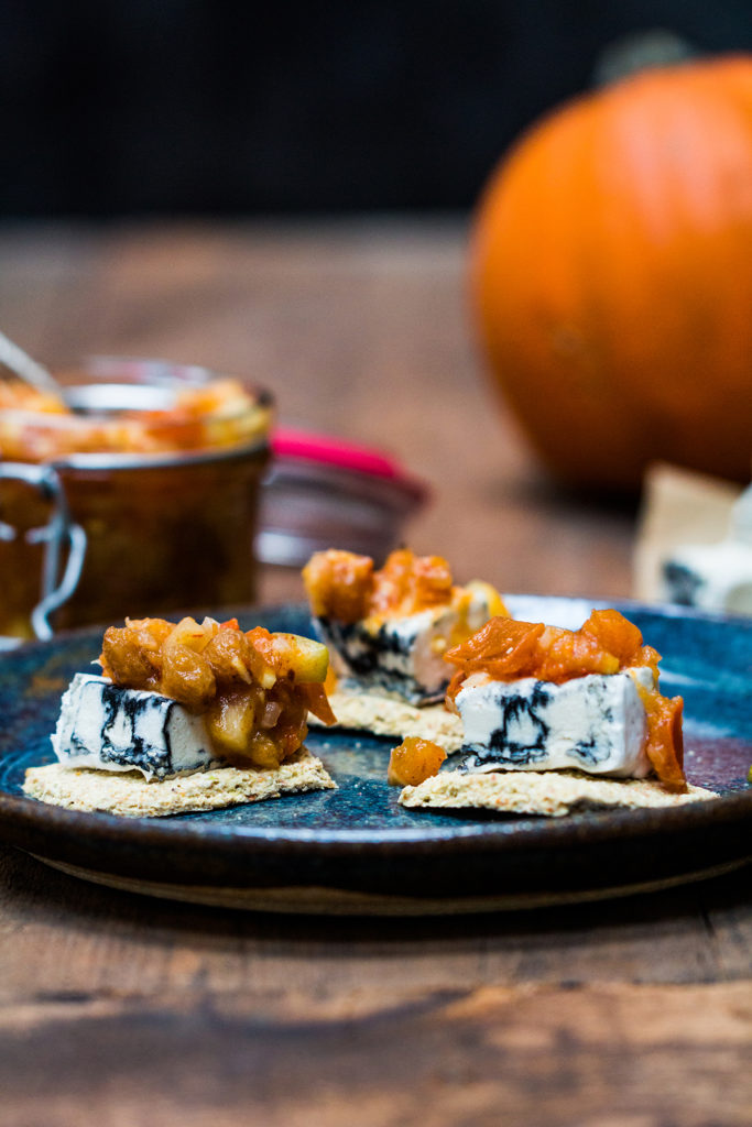 The Persimmon chutney is served as a topping for a tree nut cheese with vegan cracker. The dish is served on a blue plate.
