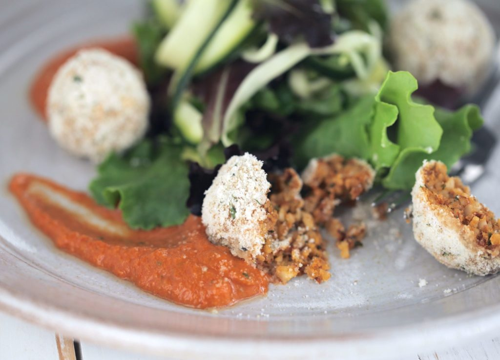 Salsa finta with almond polpetta on a grey plate with a fork and salad