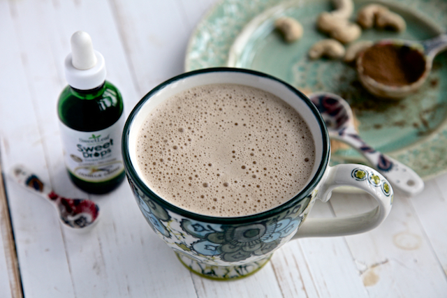 Rejuvenate latte in a mu with a bottle of stevia on a white background