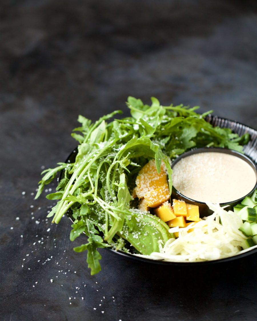 Cacao fennel rocket salad with dressing in a black bowl with a black background
