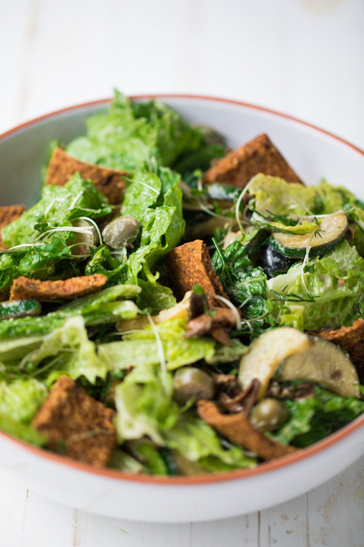 Raw sundried tomato croutons on a green leafy salad in a white bowl