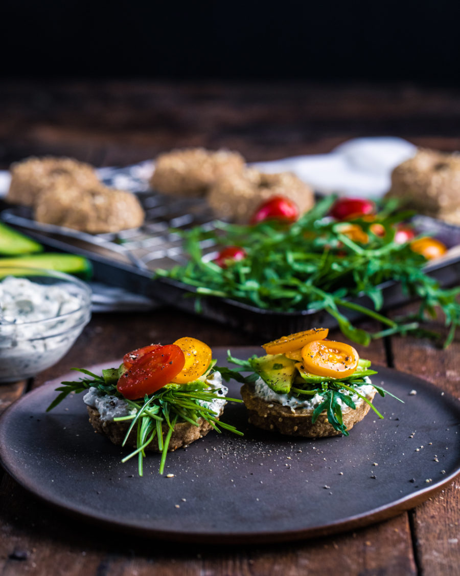 Raw vegan bagels with cashew sour cream on a plate with a wooden background