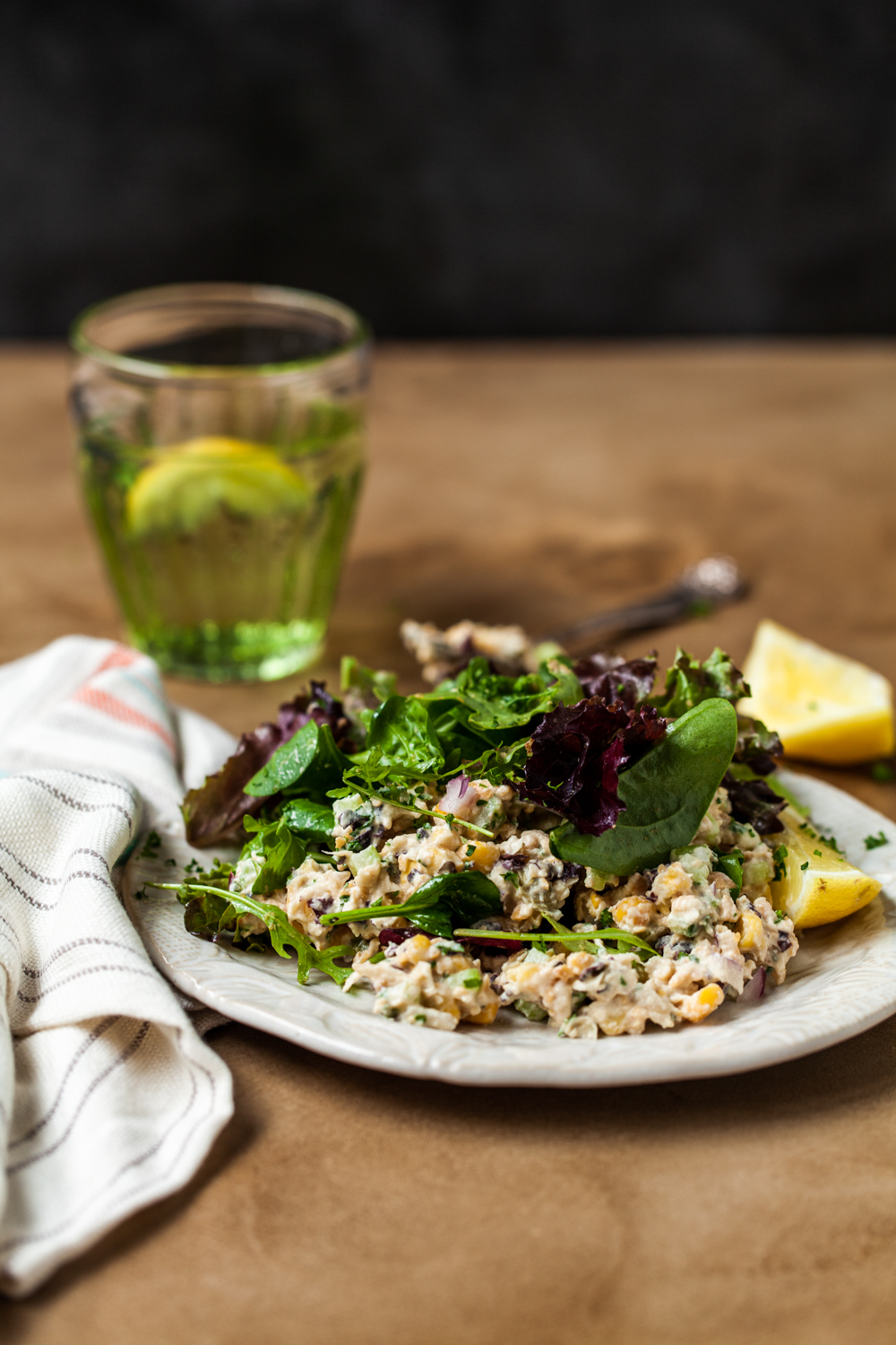 Smashed chickpea salad with green leaves on a white plate with a glass and napkin