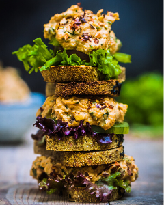 Raw bread sandwiches stacked on a wooden surface