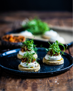 Mini raw pizzas on a black plate on a wooden surface