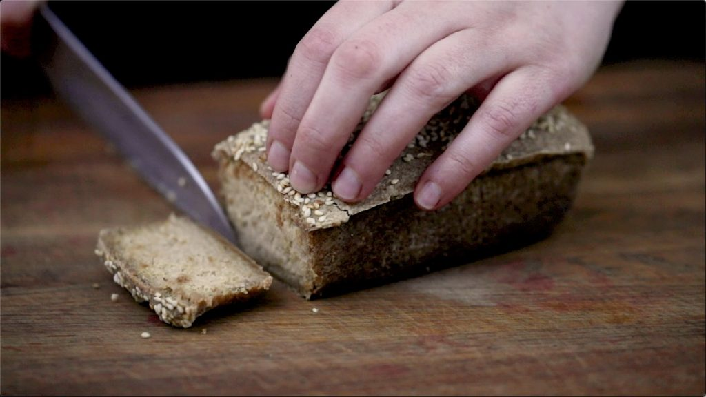 Fermented raw vegan bread loaf with one slice being cut off on a wooden chopping board