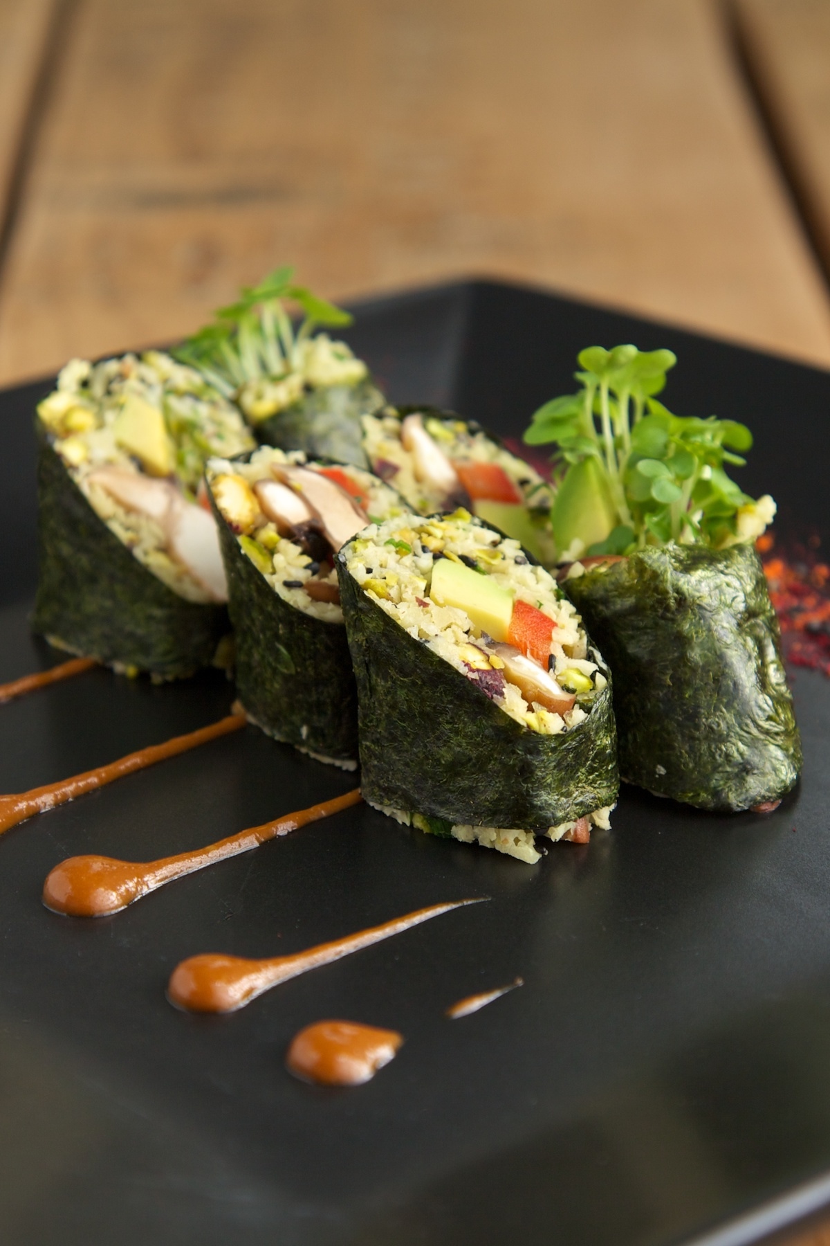Raw vegan sushi with miso sauce on a black plate