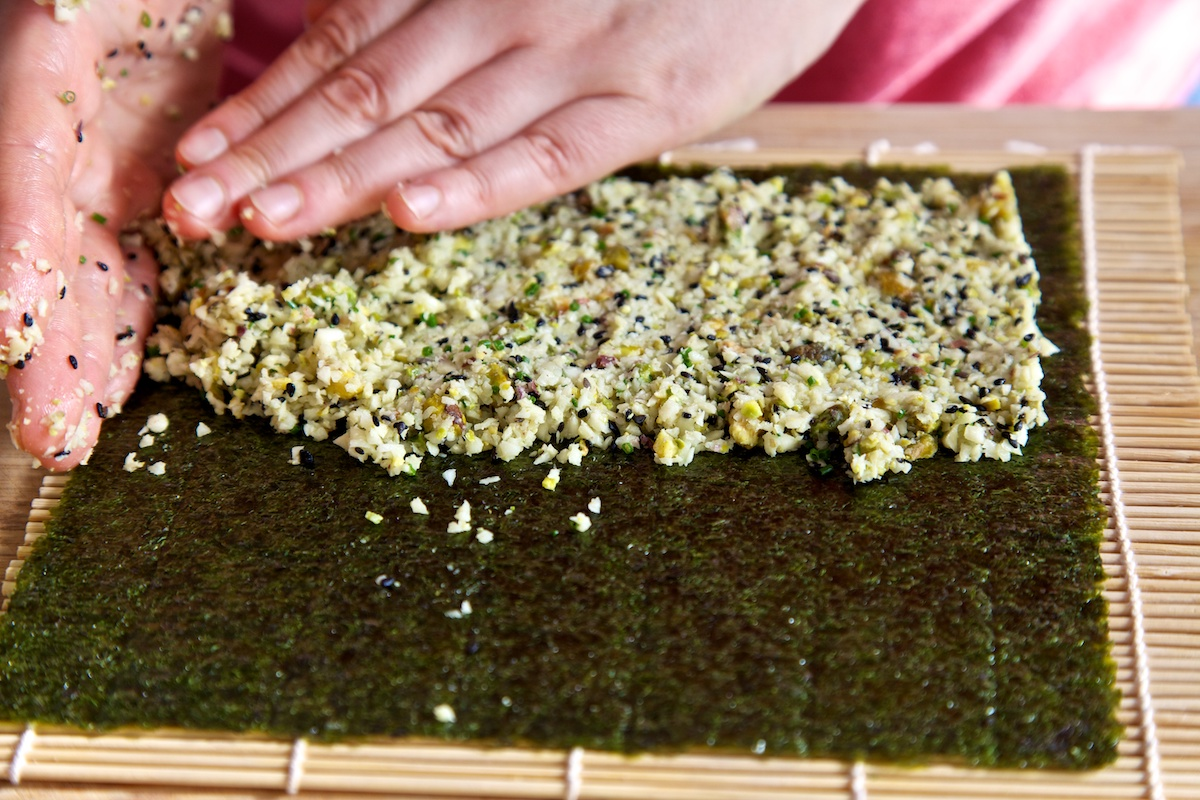 Parsnip rice being spread on top of a nori sheet, on a bamboo rolling mat