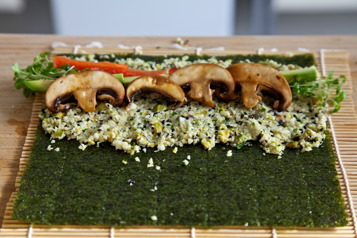 Raw vegan sushi with parsnip rice on a nori sheet, ready to roll on a bamboo mat