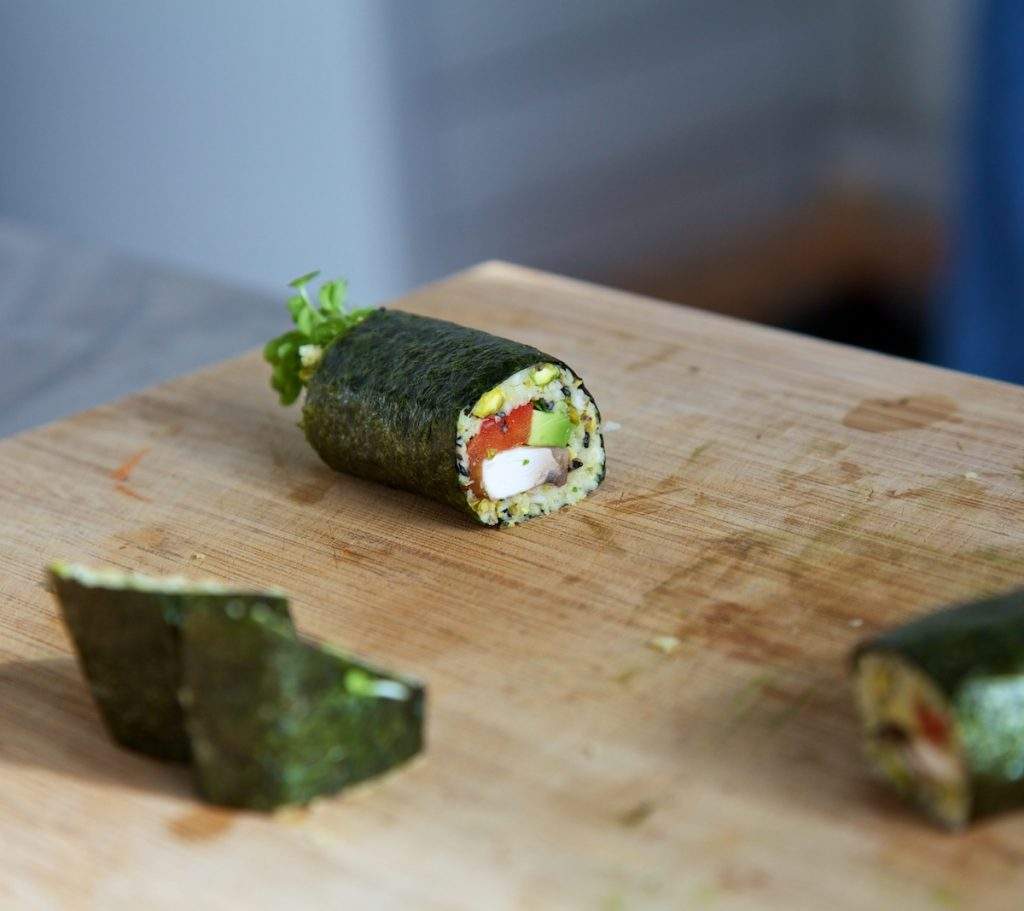 Raw vegan sushi cut into pieces on a wooden chopping board, with one piece laying down showing a cross section of the filling