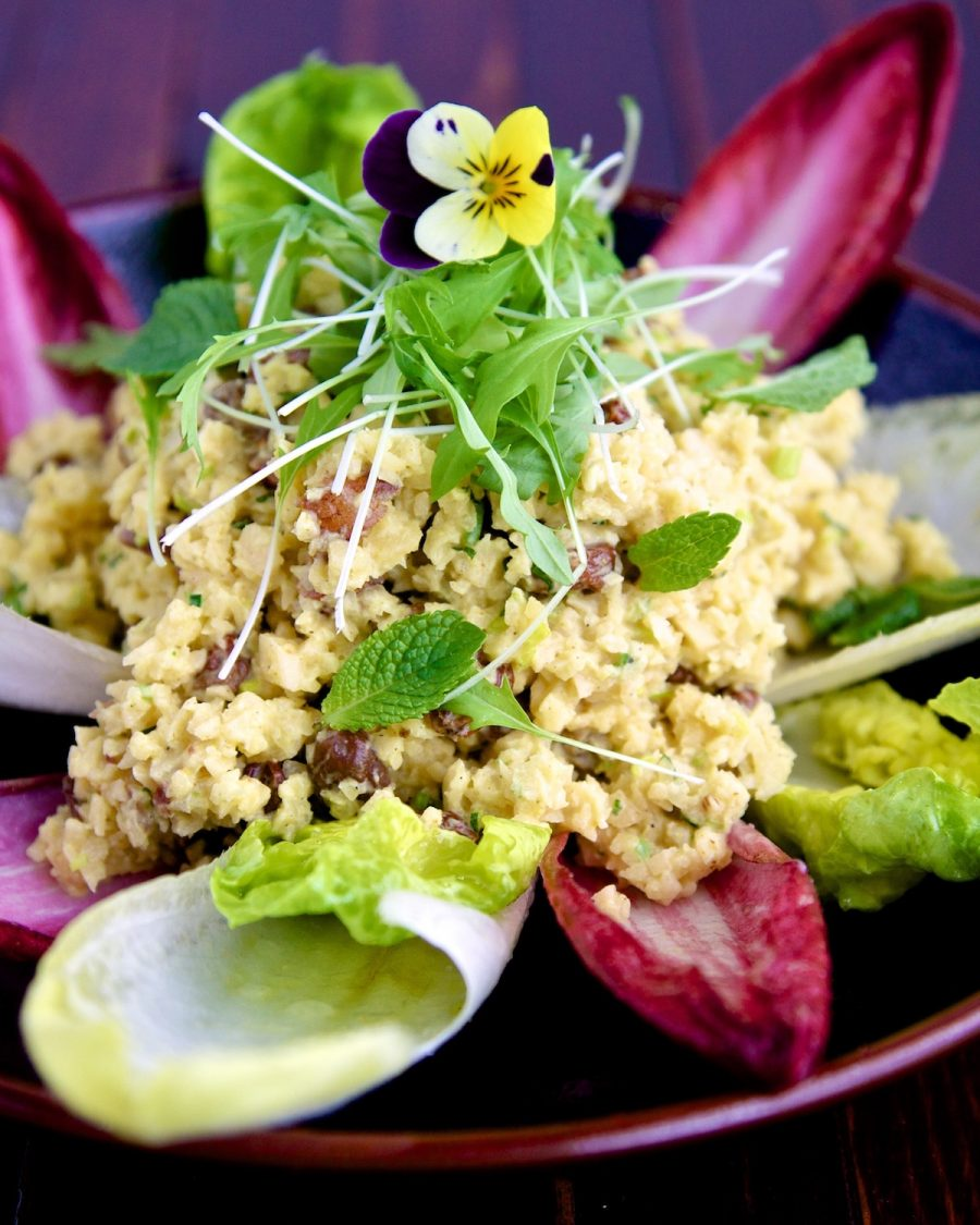 Raw food recipe of curried swede risotto on a brown place and wooden background