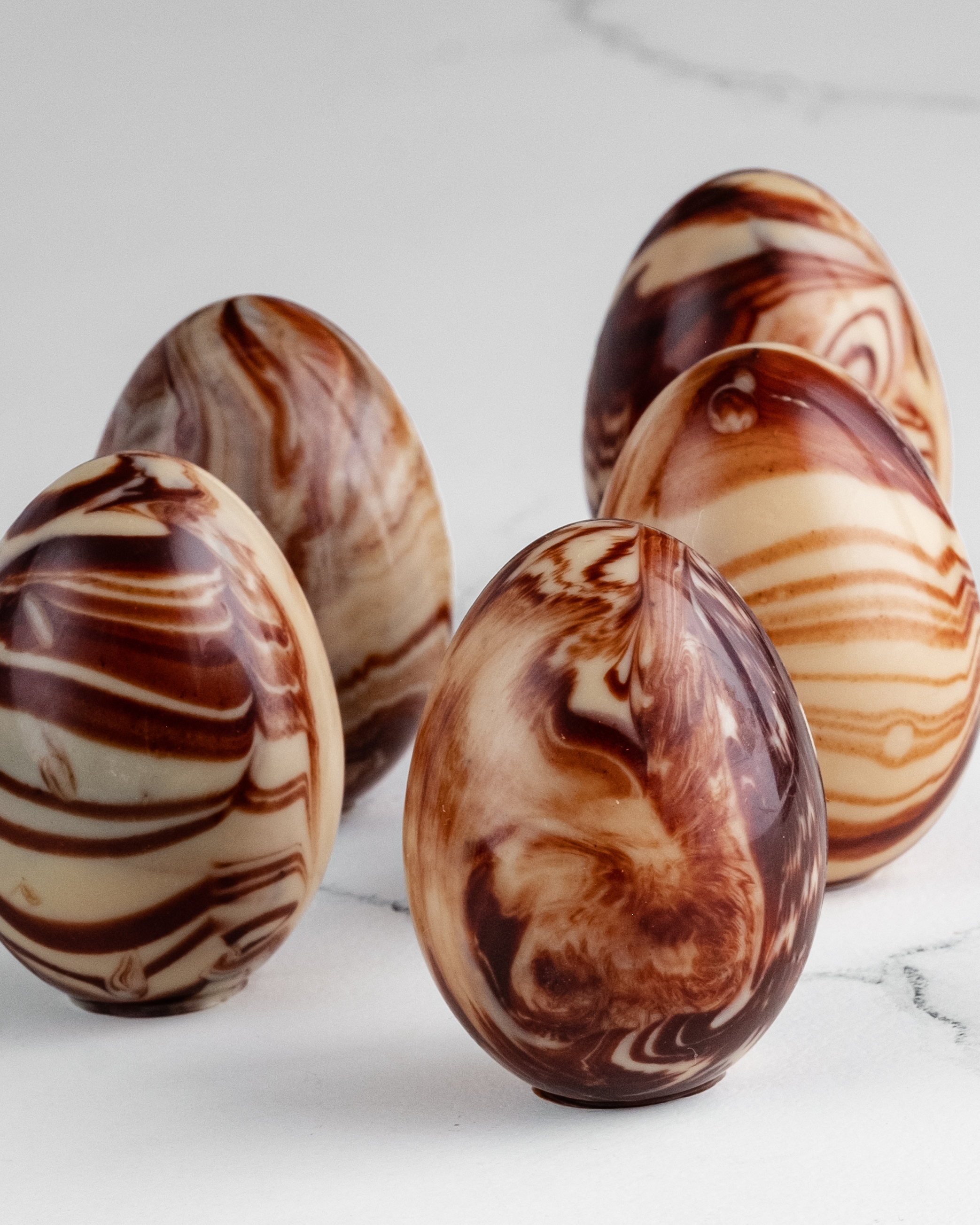 Raw chocolate marbled eggs on a white background