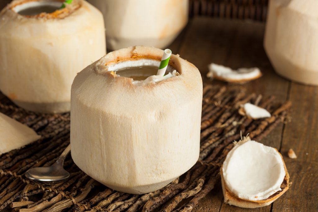 Young thai coconut open at the top with a straw in on a wooden surface
