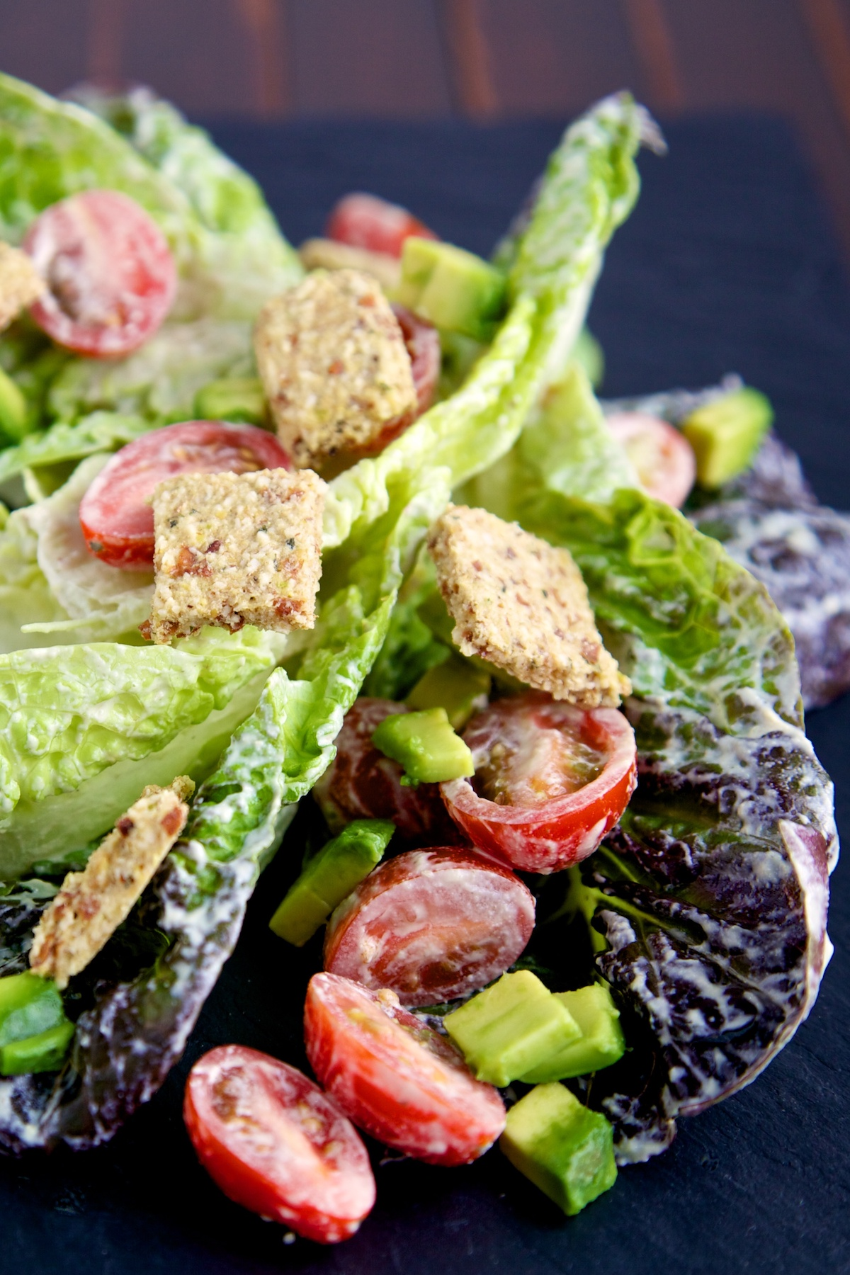 raw vegan caesar salad with croutons on a black background