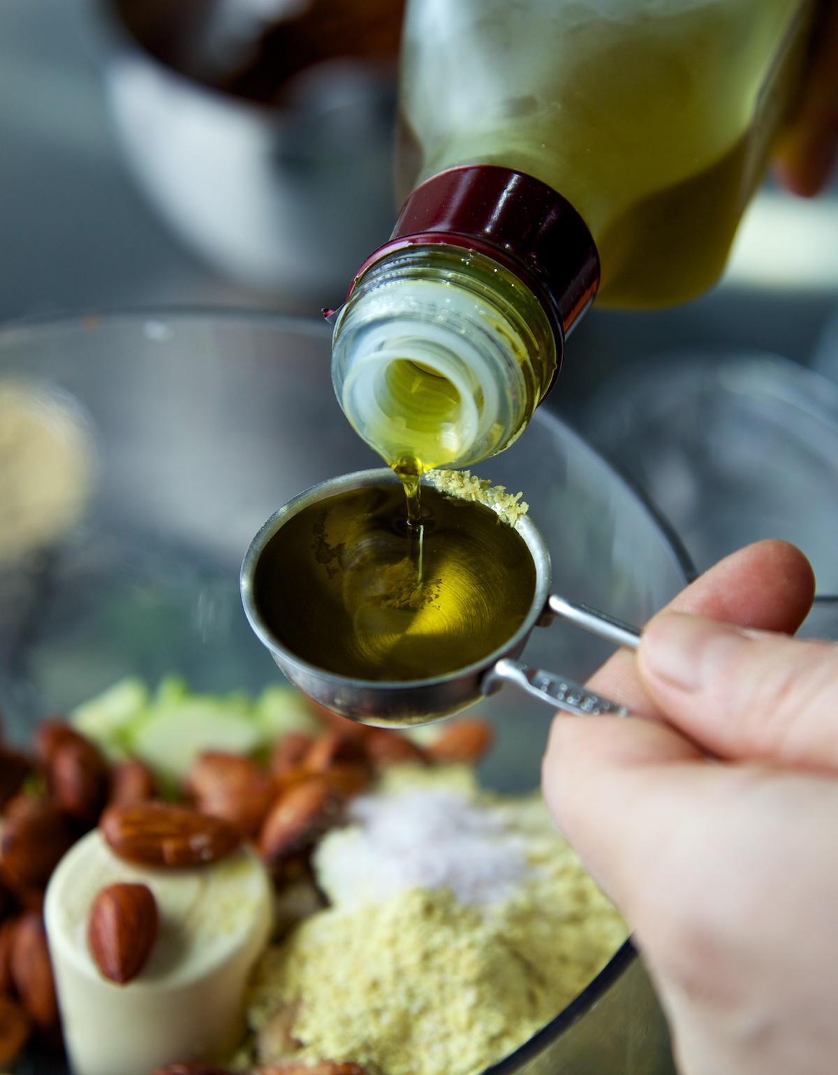 someone pouring olive oil into a measuring spoon