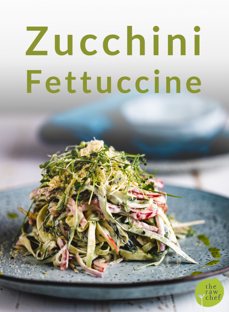 zucchini fettuccine on a blue plate and white wooden surface