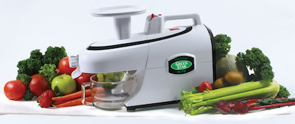 Greenstar Elite juicer on a white background surrounded by fruit and veg