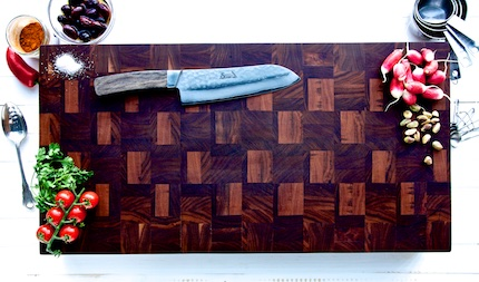 Chefs knife on a wooden chopping board with various vegetables around it