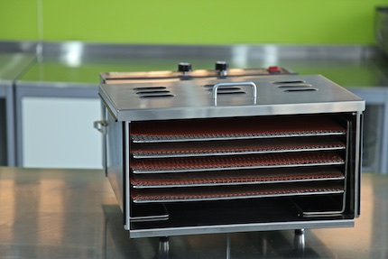 Stainless steel TSM dehydrator with the door off on a steel bench